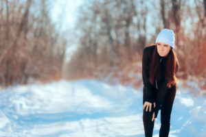 young woman with joint pain on winter background